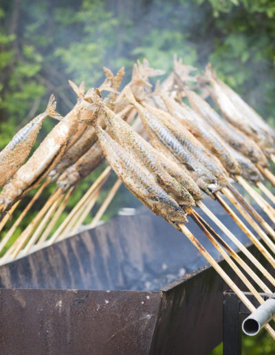 Steckerlfisch fish on a stick grilled for barbecue